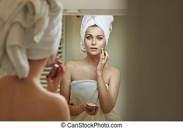 Blond woman rubbing gently a cream