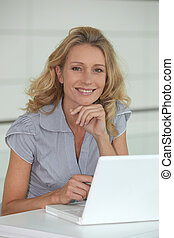 Blond woman sat at desk with laptop computer