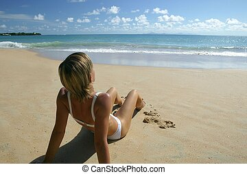 Blond woman sat on a beach
