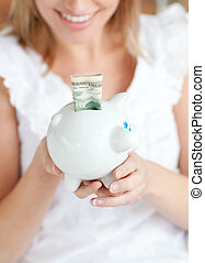 Blond woman saving money in a piggy-bank
