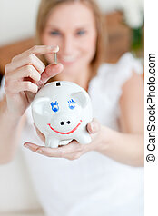 Blond woman saving money in a piggy-bank
