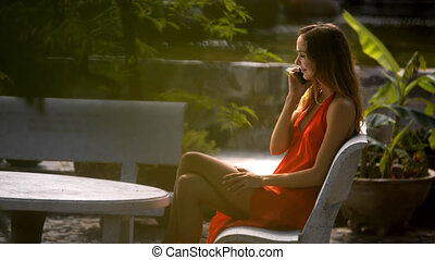 Blond Woman Sits on Bench in Park Talks on Phone