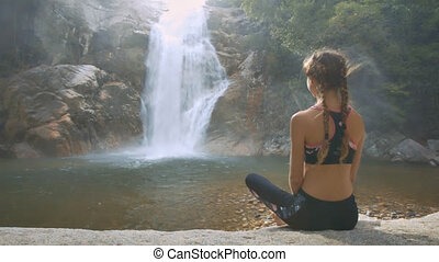 Blond Woman Sits on Stone Watches Foamy Waterfall