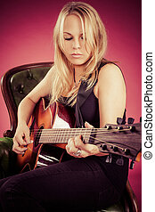 Blond woman sitting and playing guitar