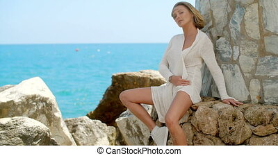 Blond Woman Sitting by Ocean Front Stone Wall