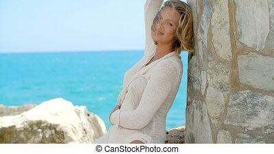 Blond Woman Sitting by Stone Wall by Windy Ocean