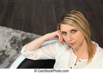 Blond woman sitting on a sofa