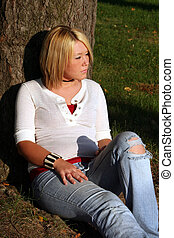 Blond Woman Sitting On Gr - Serious young blond woman...