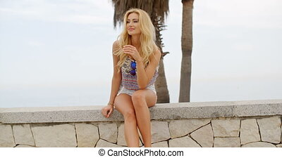 Blond Woman Sitting on Stone Wall at Beach