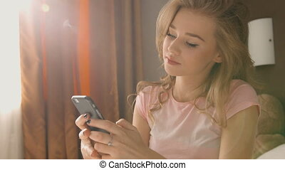 Blond woman sitting on the bed, holding her phone in hands and chatting to hear friends in a pink pajama.