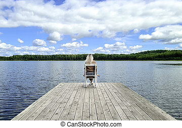 Blond woman sitting on white empty deck chair at the lake dock.