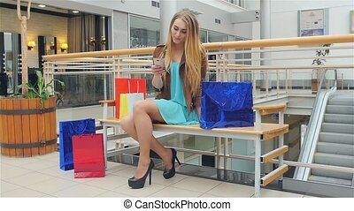 blond woman sitting shopping center with phone in his hand and writes message to someone. Slow motion