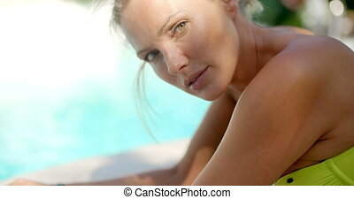 Blond Woman Smiling at Camera by Swimming Pool - Close Up of...