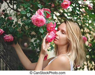 blond woman smiling in a flowering bush of pink roses