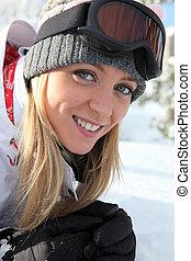 Blond woman snowboarding