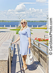 Blond woman standing on embankment in summer