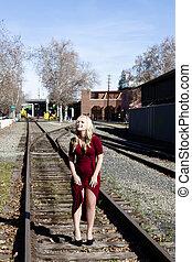 Blond Woman Standing On Rail Road Tracks Red Dress