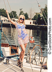 blond woman standing on yacht