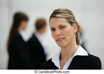 Blond woman stood with colleagues in background