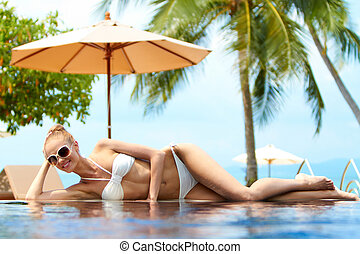 Blond woman sunbathing on an infinity pool under a beach ...