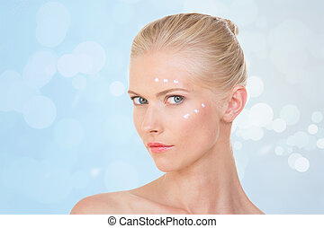 nordic girl with cream on her front and her cheekbone on blue background