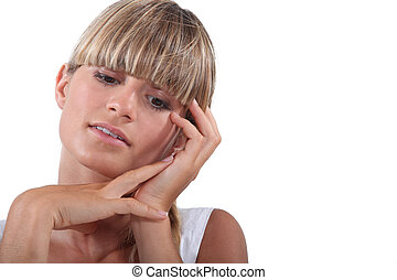 Blond woman touching face
