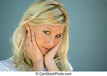 Blond woman touching her face