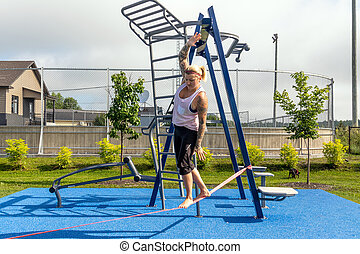 blond woman walking on a tightrope slackline at the park
