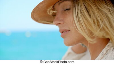 Blond Woman Wearing Hat in front of Blue Ocean
