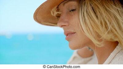 Blond Woman Wearing Hat in front of Blue Ocean