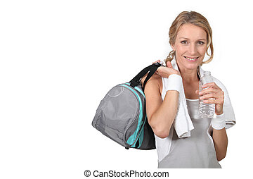 Blond woman wearing sportswear holding water bottle with bag...