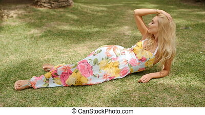 Blond Woman Wearing Sun Dress Lying in Grass - Attractive...