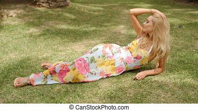 Blond Woman Wearing Sun Dress Lying in Grass