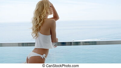 Blond woman wearing white bikini and silky top