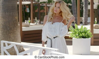 Blond Woman Wearing White Dress Looking on Patio - Waist Up...