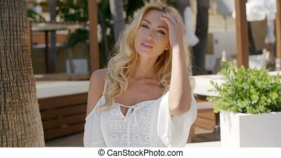 Blond Woman Wearing White Top on Resort Patio - Waist Up...