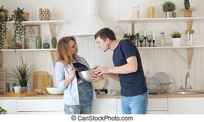 blond woman whisks food in bowl guy tastes in kitchen -...