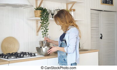 blond woman whisks in bowl on table by stove in kitchen -...