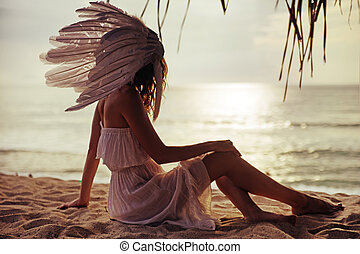 Blond woman with a huge plume watching the sunset