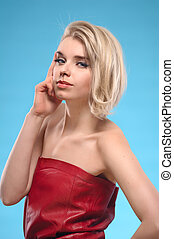 Portrait of beautiful blond woman with bare shoulders and fashion make-up on a blue background