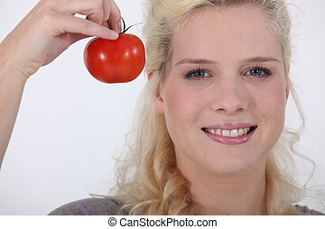 Blond woman with fresh tomato in hand