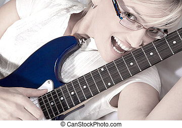 blond woman with glasses and guitar