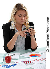 Blond woman with graphs on desk sending text message