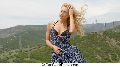 Blond Woman with Hand in Hair on Windy Hillside