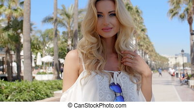 Blond Woman with Hand in Hair Outdoors