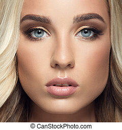 Blond woman with long curly beautiful hair. Close up face