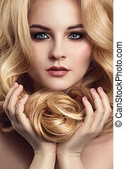 Blond woman with long curly beautiful hair. Close-up portrait.