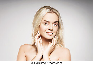 Blond woman with pure skin posing on grey background - ...