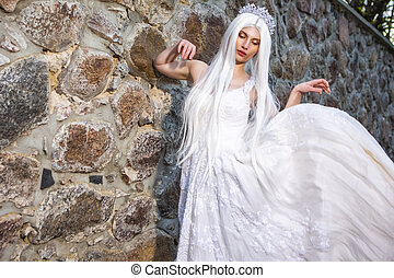Blond Woman with Tiara and Long White hair Posing in Bridal Flying Dress Against Stone Wall