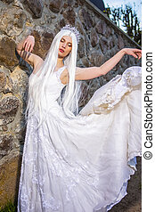 Blond Woman with Tiara and Long White hair Posing in Bridal Flying Dress Against Stone Wall.